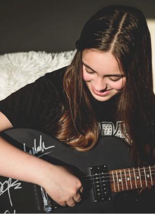 Kayia Smiling While Playing Black Guitar